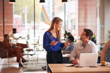 Obraz Businessman And Businesswoman Having Informal Meeting By Desk In Modern Open Plan Office - fototapety do salonu