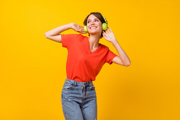 Photo of nice brunette optimistic lady listen music wear headphones red t-shirt isolated on vivid yellow color background Wall mural