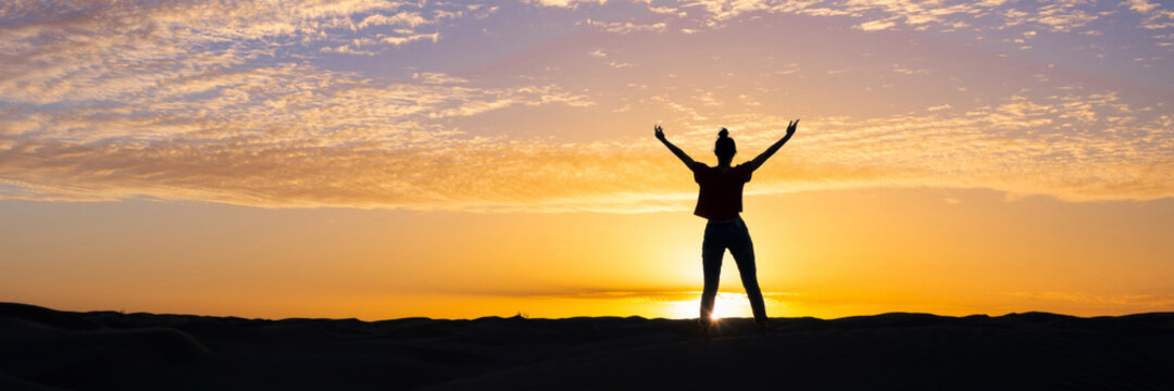Silhouette of a confident young woman standing in the sunset. Power pose panoramic background