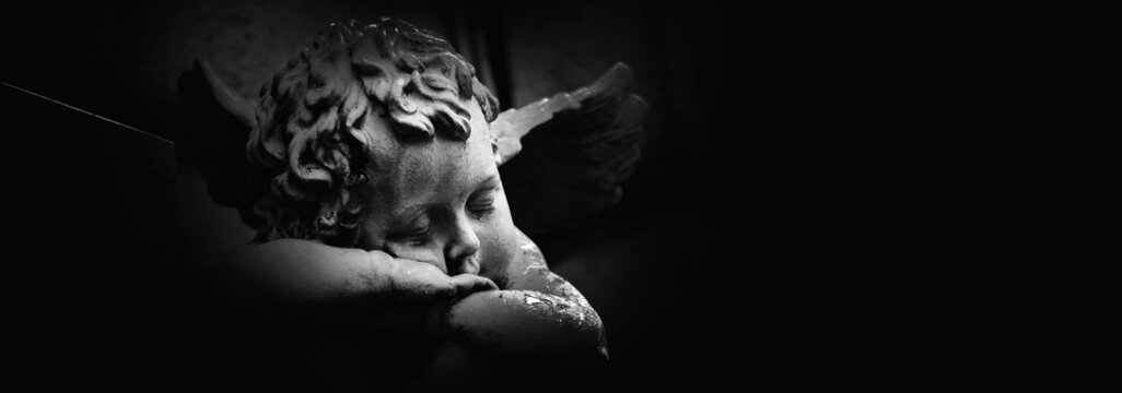 Ancient statue of  little Dreaming Angel. Copy space for design.