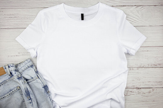 White womens cotton Tshirt mockup with blue jeans pants on wooden background. Design t shirt template, print presentation mock up. Top view flat lay.