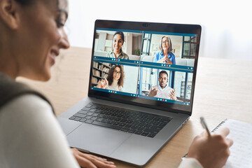 Fototapeta Happy smiling African American mixed race adult student having virtual meeting with diverse people online call elearning webinar at home office writing notes. Video e learning conference call on pc. obraz