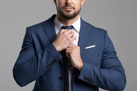 Confident professional businessman adjusting the tie