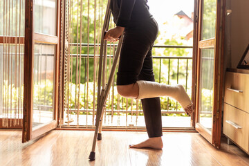 Fototapeta Close-up of a woman with a broken ankle, standing by the living room door obraz