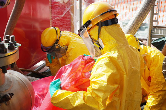 Rescue personnel wear yellow chemical protective clothing during chemical spill recover as part of emergency drills at chemical plant.