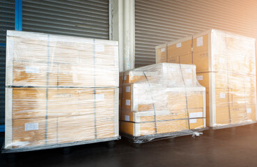 Stacked of Package Boxes Wrapped Plastic Flim on Plastic Pallets at Storage Warehouse. Shipment Boxes. Cargo Export- Import. Shipping Warehouse Logistics.