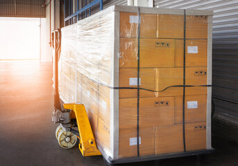 Stacked of Package Boxes Wrapped Plastic Flim on Pallet with Hand Pallet Truck. L-Shape Pallet Corrugated Paper Cardboard Angle Corner Edge Protector. Shipping Warehouse Logistics.