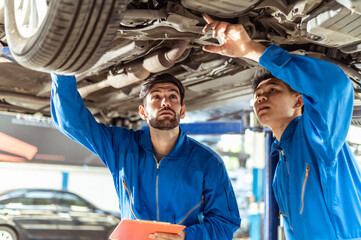 Obraz Two professional look technician inspecting car underbody and suspension system by using check list in moder car service shop. Automotive business or car repair concept. - fototapety do salonu