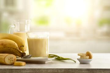 Obraz Milkshake with banana in glass cup on table kitchen background - fototapety do salonu