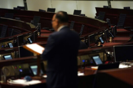 Empty seats of pro-democracy legislators are seen in the background during a meeting to debate on electoral reform bill at Legislative Council in Hong Kong