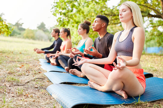 Group of friends doing meditation in the lotus position