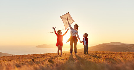 Fototapeta Happy family  mother and kids  launch  kite on nature at sunset obraz