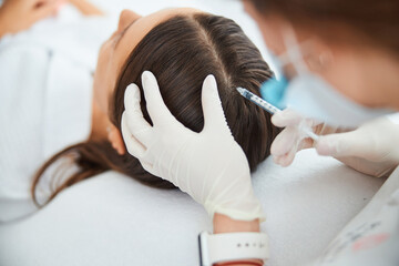 Obraz Dermatologist injecting the serum into the female scalp - fototapety do salonu