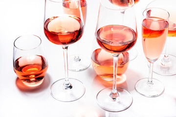 Obraz Rose wine glasses set on wine tasting. Different varieties, colors and shades of pink wines on white background. Top view - fototapety do salonu