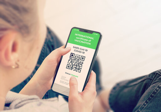 COVID-19: Digital green certificates on Cellphone Screen. Young Girl Takes Smartphone with Vaccinated digital health passport.