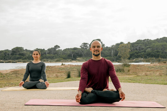 woman with dark hair and bald man, practicing yoga in nature park, lotus pose and relaxation transformation, morning exercise