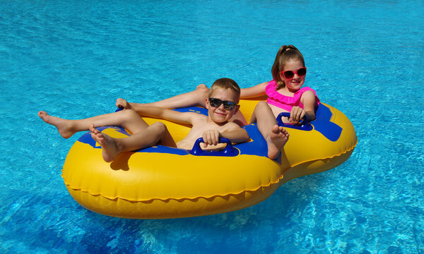 Boy and girl on inflatable float in outdoor swimming pool.