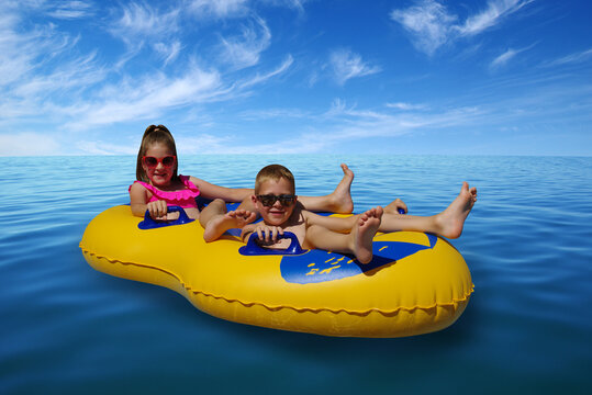 Boy and girl on inflatable float in blue sea water.