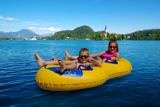 Boy and girl on inflatable float in lake. Little children floating in yellow raft on surface water.