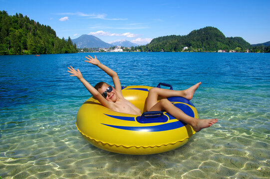 Little boy on inflatable ring in the lake .