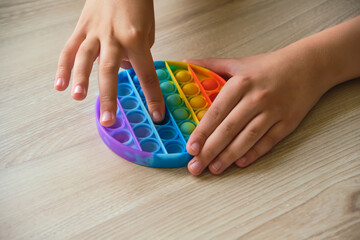 Anonymous child playing with the colorful pop It toy.