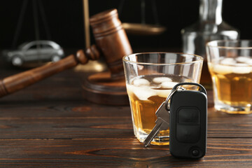Fototapeta Car key, glass of alcohol near gavel on wooden table, space for text. Dangerous drinking and driving obraz