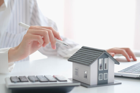 close up hand with house model for real estate check and summary expense of home loan mortgage for refinance plan, insurance or loan real estate.