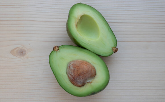 Slices of ripe avocado lie on a light cutting board