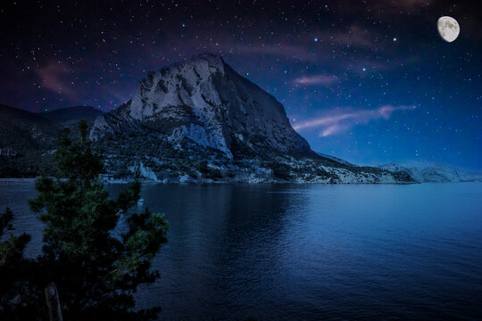 Moonlit starry night over the bay. Mount Sokol (Falcon). Bay on the Black Sea in Crimea, Russia, Novy Svet. Pines growing on the slopes of the mountain. Bright moon. Many stars in the sky.