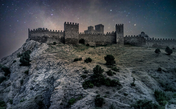 Medieval castle on a high rock at night. Stars on the sky. Medieval Genoese fortress in Crimea, Russia. Starry night in summer. Shrub growing on rocks. Ancient Fortress in Sudak.