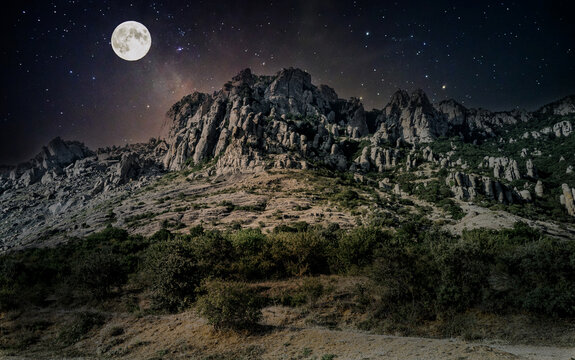 Full moon and stars over Mount Demerdzhi in Crimea in Russia. Milky Way in the sky. Summer night in the mountains. Shrubs growing on the mountain slopes. The rocks