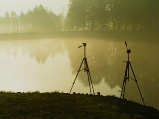 Fototapeta Poranek, wschód słońca plener nad wodą, ze statywami fotograficznymi obraz
