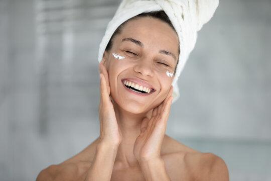 Happy excited beautiful girl enjoying facial skincare procedures, applying nourishing cream for smooth silky eye skin, massaging face with fingers, with closed eyes, smiling, laughing, Head shot