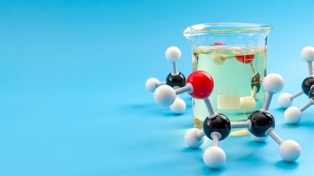 Molecular structure of chemical compounds and organic chemistry concept with educational plastic model of ethanol molecules and glass flask isolated on blue background with copy space