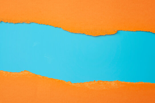 Horizontal border and colorful backgrounds concept with torn orange paper and copy space on blue background
