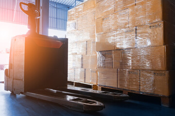 Stacked of Package Boxes on Pallet with Forklift Pallet Jack in Storage Warehouse. Shipping Warehouse Logistics.