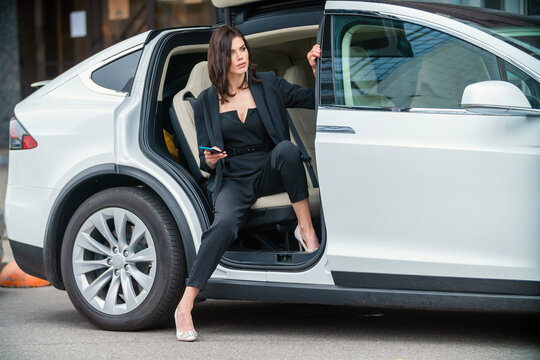 a woman in a business suit sits in the back seat of a car