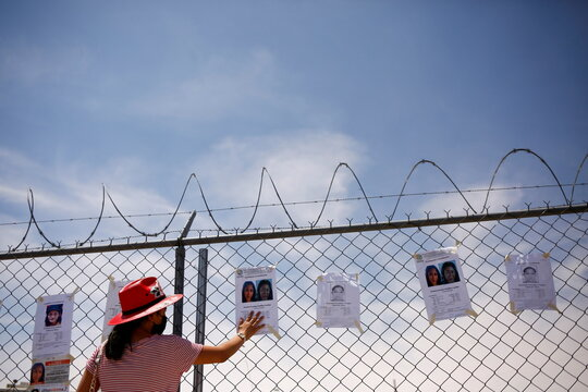 A woman touches a poster with a photo of a missing young woman during a protest in front of a prison in Ciudad Juarez