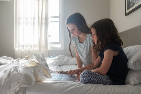 Closeup Of Little Girls Sitting On Bed Looking At Laptop With Bright Light From Window