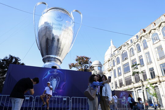 People are seen taking pictures next to an inflatable model of the Champions League cup in Porto's central Aliados square as thousands of English fans make their way to Portugal's northern city for the League's final match and hotels and bars hope for a bo
