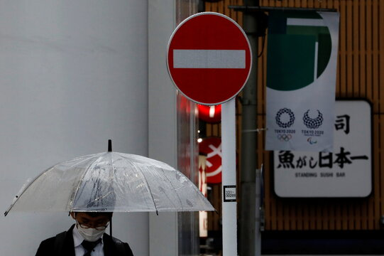 A man wearing a protective mask, following the coronavirus disease (COVID-19) outbreak, stands in front of Tokyo 2020 Olympic Games flag in Tokyo