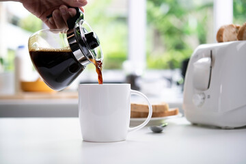 A hand pouring steaming coffee in to a cup on table in the kitchen