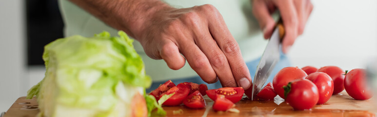 Fototapeta partial view of man cutting fresh vegetables in kitchen, banner obraz