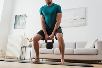 Fototapeta cropped view of barefoot man lifting kettlebell at home obraz