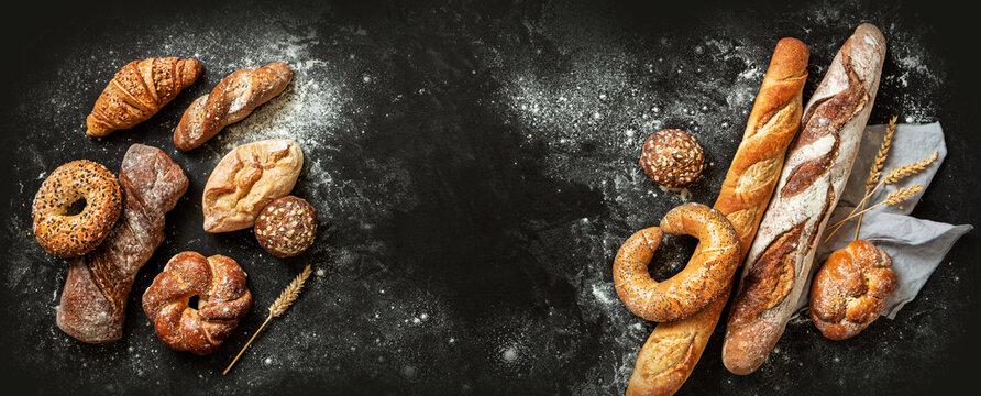 Bakery - bread rolls, baguette, bagel, sweet bun and croissant on black background