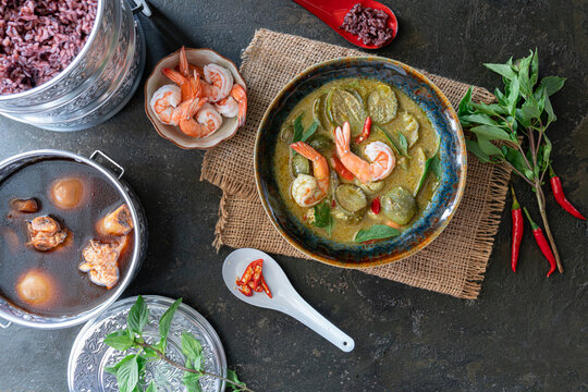 Thailand tradition Green curry with shrimp with stewed pork leg with rice. Thai cuisine. (kang keaw wan). on old kitchen table with copy space.