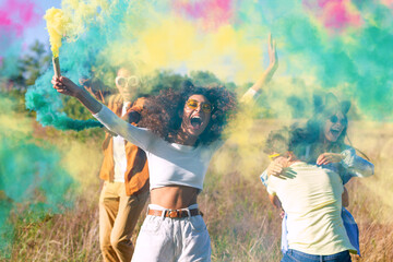 Beautiful young man and woman hold light up colored smoke bombs - Happy friends having fun in the park with multicolored smoke bombs - Young students celebrating spring break together. Holi festival. - fototapety na wymiar