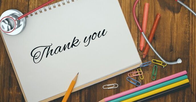 Composition of notebook with thank you note, with stethoscope, stationery and pencils on wooden desk
