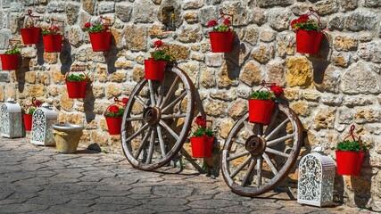 Obraz Czerwone doniczki z kwiatami na kamiennym murze w greckim miasteczku - fototapety do salonu