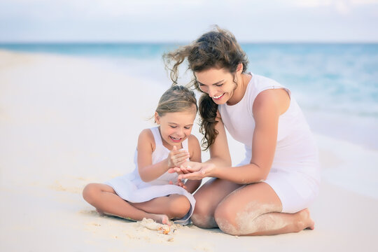 Mother with little daughter playing on ocean beach, Maldives. Family on the beach concept.